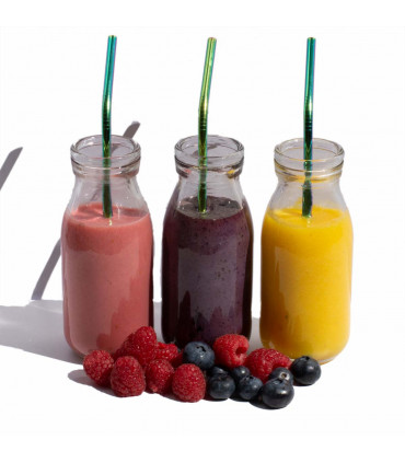 Three glass bottles with smoothies and stainless steel reusable straws