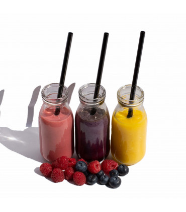 Three glass bottles with beverages in it and stainless steel straws