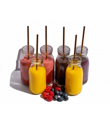 Six glass jars of colored smoothies with stainless steel straws