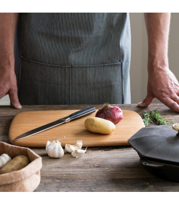 Medium cutting board with patatoe, ognion and knife on it in front of cook