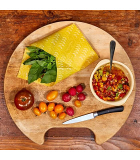Food wrapped in beeswax wrap with tomatoes on wooden serving plate