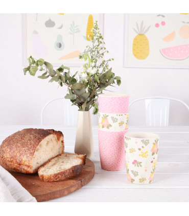 Three stacked Love Mae floral pattern and pink colored bamboo tumblers with bread on the side