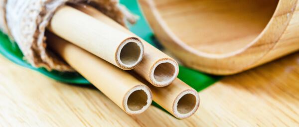 Quatre pailles en bambou posé sur une feuille de bananier à coté d'un gobelet en bambou