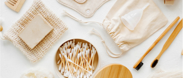 Bamboo cotton buds, wooden comb, soap bar, bamboo toothbrush, soap holders, menstrual cup and loofah soap holder in a plastic free bathroom