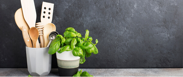 Kitchen utensils in a pot with basil plant on its right