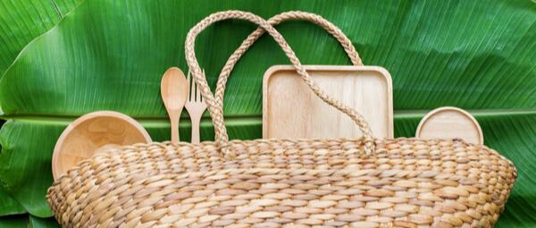Panier de pique nique en osier avec couverts, plats, assiettes et planche sur feuille de palmier
