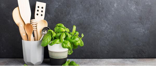 Ustensiles de cuisine dans un pot et une plante de basilic